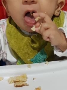 Bebé comiendo trocitos de comida con las manos